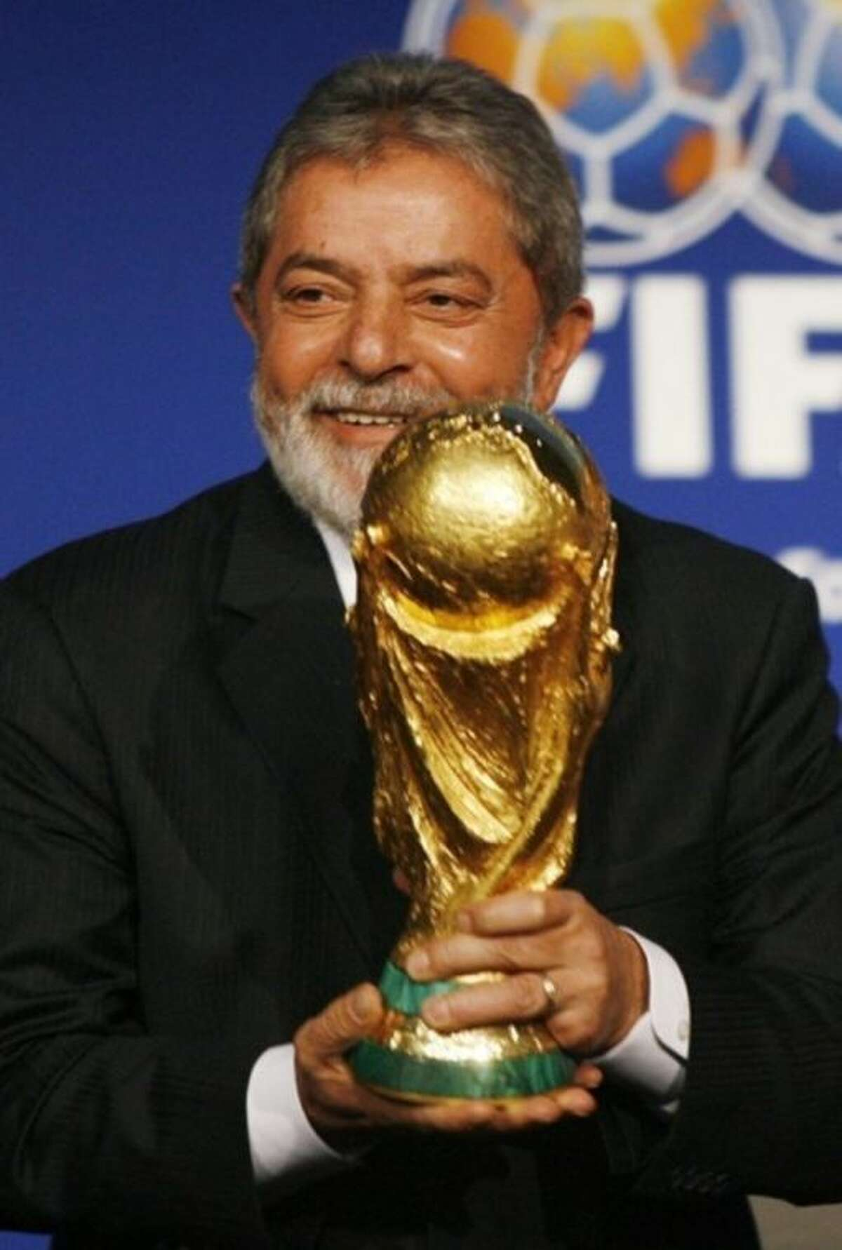 FILE - In this 30 October, 2007, file photo, Brazilian President Lula holds the World Cup Trophy after it was announced that Brazil will host the 2014 Soccer World Cup in Zurich, Switzerland. Lula, the country?'s immensely popular and folksy former leader told the crowd at celebratory ceremony in Zurich that he would return home full of joy but also feel the burden of hosting the world?'s biggest sporting event. The tournament opens June 12 with Brazil facing Croatia in the opening match. (KEYSTONE/Steffen Schmidt, File)
