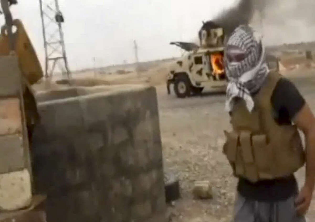 This image made from video posted by Iraqi0Revolution, a group supporting the al-Qaida breakaway Islamic State of Iraq and the Levant (ISIL) on Wednesday, June 12, 2014, which has been verified and is consistent with other AP reporting, shows a militant standing in front of a burning Iraqi Army Humvee in Tikrit, Iraq. The al-Qaida-inspired group that led the charge in capturing two key Sunni-dominated cities in Iraq this week has vowed to march on to Baghdad, raising fears about the Shiite-led government?'s ability to slow the assault following lightening gains. Fighters from ISIL on Wednesday took Saddam Hussein's hometown of Tikrit, as soldiers and security forces abandoned their posts and yielded ground once controlled by U.S. forces. (AP Photo/Iraqi0Revolution via AP video)
