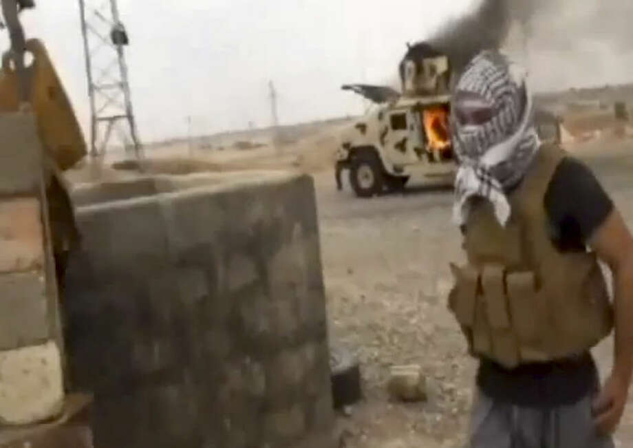 This image made from video posted by Iraqi0Revolution, a group supporting the al-Qaida breakaway Islamic State of Iraq and the Levant (ISIL) on Wednesday, June 12, 2014, which has been verified and is consistent with other AP reporting, shows a militant standing in front of a burning Iraqi Army Humvee in Tikrit, Iraq. The al-Qaida-inspired group that led the charge in capturing two key Sunni-dominated cities in Iraq this week has vowed to march on to Baghdad, raising fears about the Shiite-led government's ability to slow the assault following lightening gains. Fighters from ISIL on Wednesday took Saddam Hussein's hometown of Tikrit, as soldiers and security forces abandoned their posts and yielded ground once controlled by U.S. forces. (AP Photo/Iraqi0Revolution via AP video)