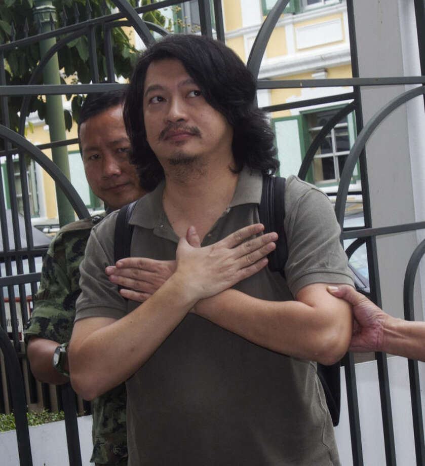 "Sombat Boonngam-anong gestures a sign of freedom upon arriving at the military court in Bangkok, Thailand, Thursday, June 12, 2014. Sombat was arrested last Thursday after failing to report himself to the authorities as was ordered by the military government that took power in Thailand last month. A prominent social activist, he had spearheaded an online campaign calling for people to silently show opposition to the coup by raising a three-finger salute in public places - borrowing a symbol of resistance to oppression from Hollywood's ""The Hunger Games."" By defying the order to surrender, he made himself liable to trial by a military court and a possible two-year jail sentence. (AP Photo/Sakchai Lalit)"