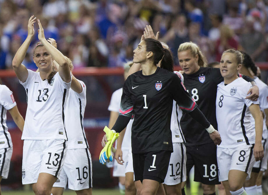 United States' Alex Morgan (13) and goalkeeper Hope Solo (1) salute the crowd after the U.S. team defeated Germany 2-0 in a semifinal in the Women's World Cup soccer tournament, Tuesday, June 30, 2015, in Montreal, Canada. (Graham Hughes/The Canadian Press via AP)