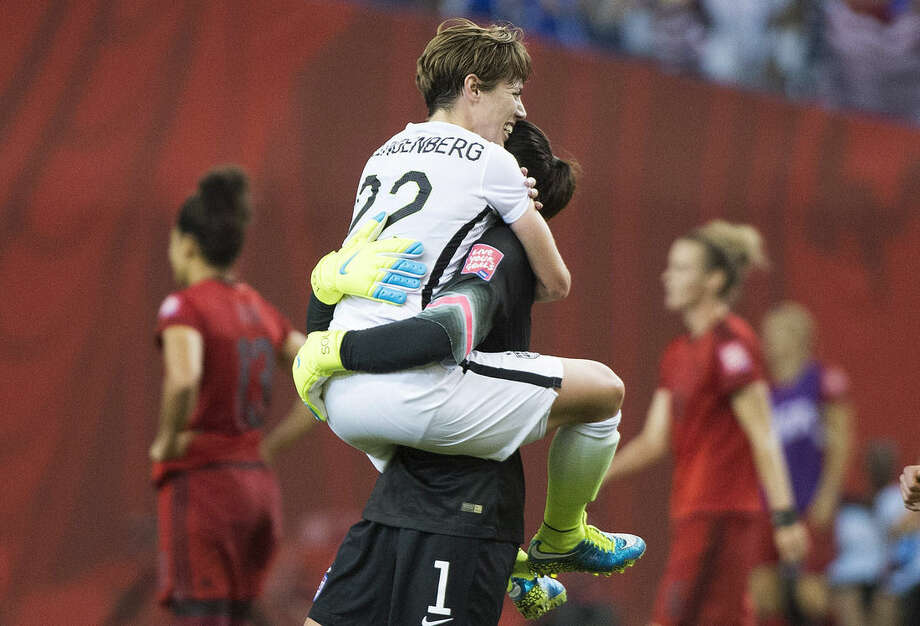 U.S. goalie Hope Solo and Meghan Klingenberg (22) celebrate after the team defeated Germany in a semifinal in the Women's World Cup soccer tournament, Tuesday, June 30, 2015, in Montreal, Canada. The United States won 2-0. (Graham Hughes/The Canadian Press via AP)