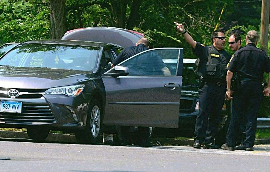 Hour photo/Erik TrautmannNorwalk police search a Toyota Camry following the apprehension of an armed robbery suspect on Wilson Ave Wednesday.
