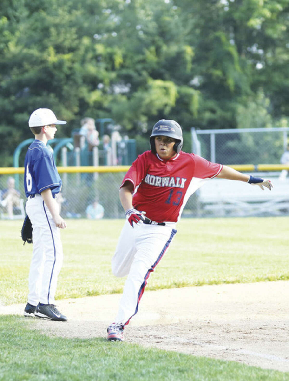Hour photo/Danielle Calloway Norwalk's Trevor McGee, rounds third base and heads for home in Norwalk's 13-3 win over Darien American on Wednesday.