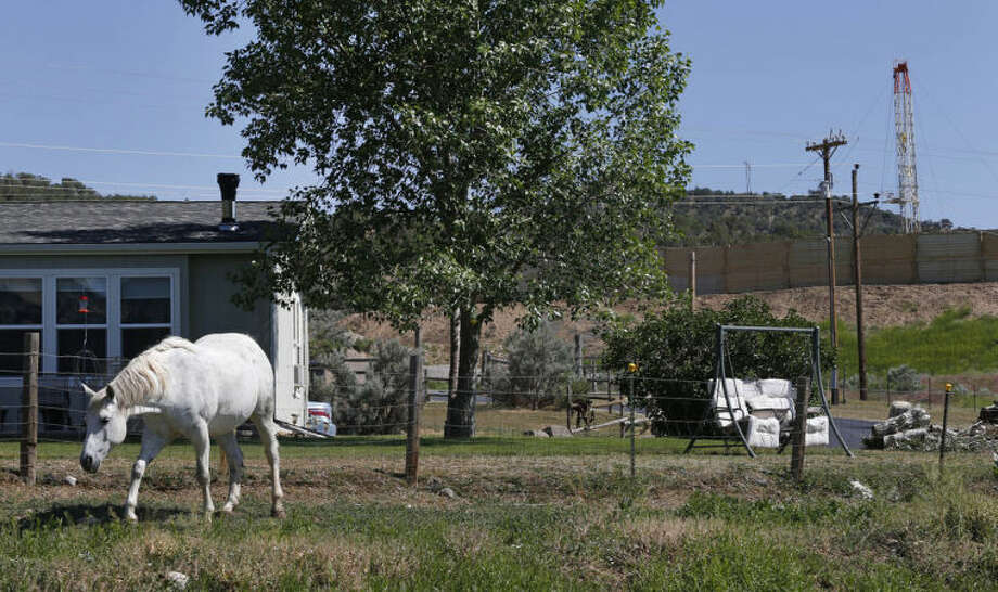 ADVANCE FOR SUNDAY, JUNE 15 AND THEREAFTER - This photo taken June 9, 2014 shows a horse named Primo grazing in front of the home of local resident Joann Aramillo, with an oil and gas rig on a well pad visible a few hundred yards away, top right, in New Castle, a small farming and ranching settlement on the Western Slope of the Rockies, in Colo. Four in 10 new oil and gas wells near national forests and fragile watersheds or otherwise identified as higher pollution risks escape federal inspection, unchecked by an agency struggling to keep pace with America's drilling boom, according to an Associated Press review that shows wide state-by-state disparities in safety checks. (AP Photo/Brennan Linsley)