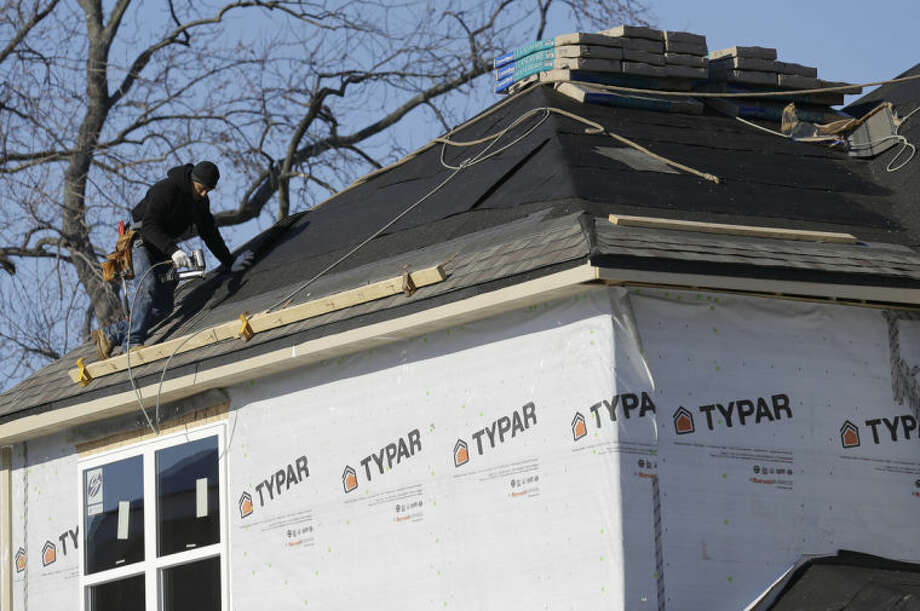 FILE - In this Friday, Dec. 27, 2013, photo, a construction worker roofs a new home in Wilmette, Ill. Many skilled workers needed to put up a home fled to other careers after the housing collapse several years ago. Now, there aren't enough of them as the housing market recovers. (AP Photo/Nam Y. Huh, File)