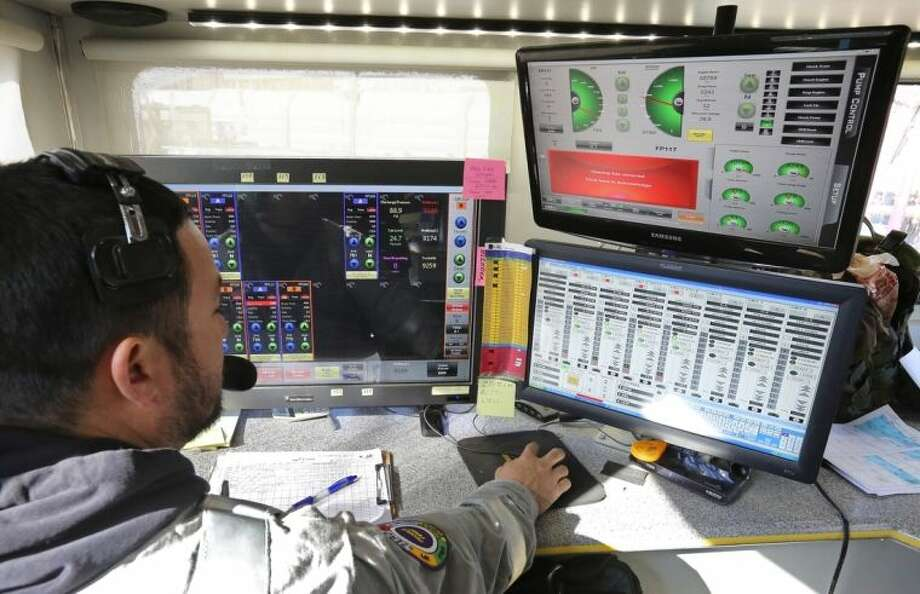 FILE - In this March 25, 2014 file photo, a technician inside a trailer monitors and directs the pressure and mix of water, sand and chemicals pumped during a hydraulic fracturing operation at an Encana Corp. well pad near Mead, Colo. Oil and gas workers earned an average 11 percent more an hour in April than they did a year ago, according to the Bureau of Labor Statistics. That's more than five times the average gain across all industries. (AP Photo/Brennan Linsley, File)