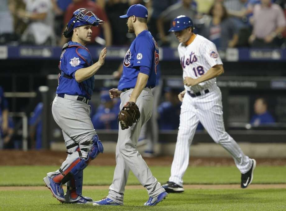 Chicago Cubs catcher David Ross, left, celebrates with relief pitcher Justin Grimm, center, as New York Mets third base coach Tim Teufel (18) runs past them after a baseball game Wednesday, July 1, 2015, in New York. The Cubs won 2-0. (AP Photo/Frank Franklin II)
