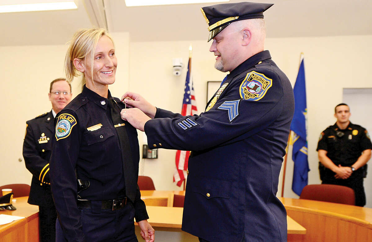 Wilton police Officer Eva Zimnoch is pinned by her brother, Meriden police Sgt. Lester Zimnoch, after being promoted to the rank of detective during a swearing-in ceremony Thursday morning.