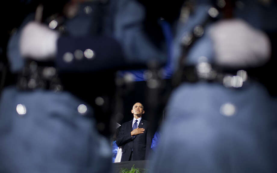 President Barack Obama places his hand over his chest during the playing of the National Anthem prior to delivering the commencement address at Worcester Technical High School, Wednesday, June 11, 2014, in Worcester, Mass. (AP Photo/Pablo Martinez Monsivais)