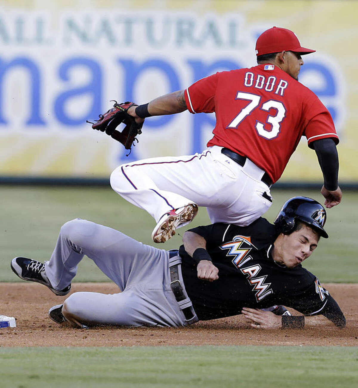 Texas Rangers second baseman Rougned Odor (73) lands on Miami Marlins Christian Yelich at second base turning a double play during the third inning of a baseball game in Arlington, Texas, Wednesday, June 11, 2014. Marlins Ed Lucas was out at first. (AP Photo/LM Otero)