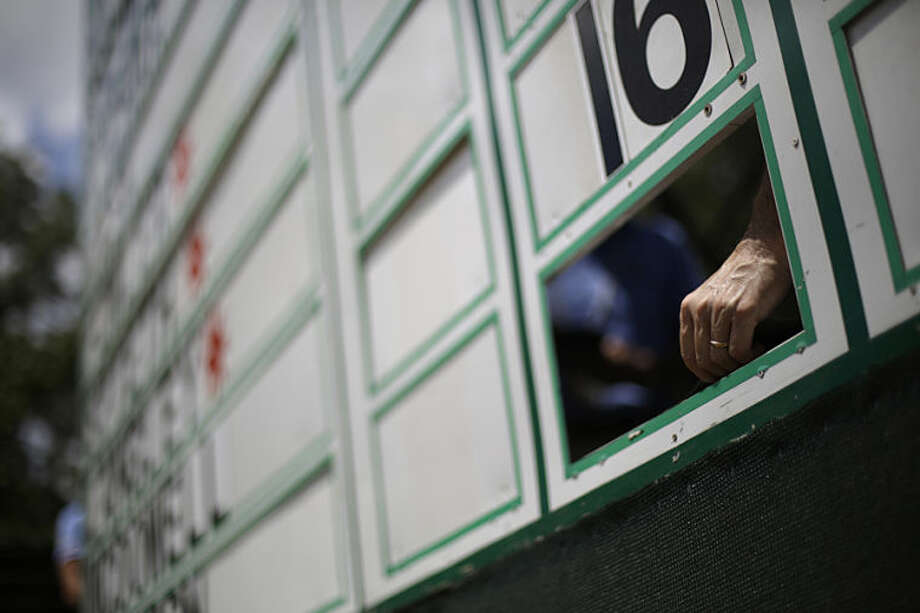 A score keeper fixes the leaderboard on the 17th hole during the first round of the U.S. Open golf tournament in Pinehurst, N.C., Thursday, June 12, 2014. (AP Photo/David Goldman)