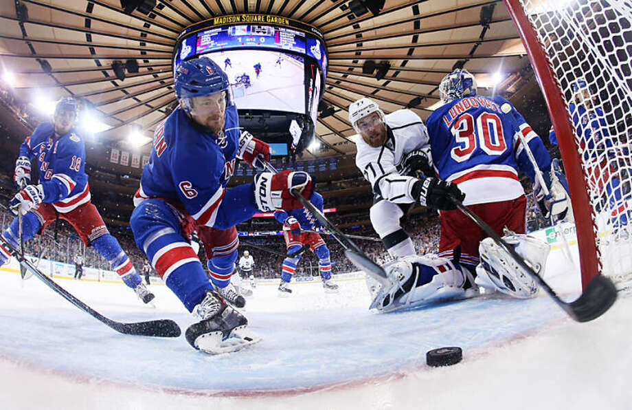 New York Rangers defenseman Anton Stralman (6) reaches to save the puck from crossing the goal line as Los Angeles Kings center Jeff Carter (77) tries to score from behind New York Rangers goalie Henrik Lundqvist (30) in the first period during Game 4 of the NHL hockey Stanley Cup Final, Wednesday, June 11, 2014, in New York. (AP Photo/Bruce Bennett, Pool)