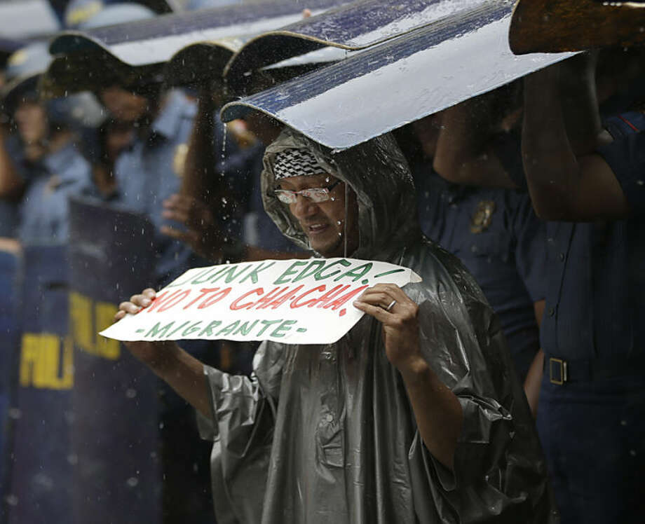 A protester takes shelter with riot police during a sudden downpour while holding a rally near the US Embassy in Manila, Philippines Thursday, June 12, 2014 to protest the recent agreement signed by the U.S. and the Philippines known as EDCA or Enhanced Defense Cooperation Agreement. The agreement will allow back US troops and the use of some Philippine military bases and facilities. Cha-Cha means Charter Change. (AP Photo/Bullit Marquez)