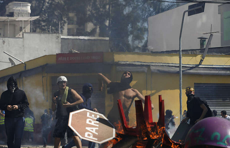 A protester throws a stone at police from behind a burning barricade during clashes in Sao Paulo, Brazil, Thursday, June 12, 2014. Brazilian police clashed with anti-World Cup protesters trying to block part of the main highway leading to the stadium that hosts the opening match of the tournament. (AP Photo/Dario Lopez-Mills)