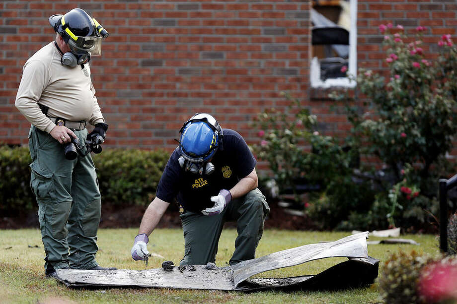 Investigators from the Bureau of Alcohol, Tobacco, Firearms and Explosives and the South Carolina Law Enforcement Division piece together parts of a charred door, doorknob and lock outside Mount Zion African Methodist Episcopal church, Wednesday, July 1, 2015, in Greeleyville, S.C. The African-American church, which was burned down by the Ku Klux Klan in 1995, caught fire Tuesday night, but authorities said arson is not the cause. (Veasey Conway/The Morning News via AP)