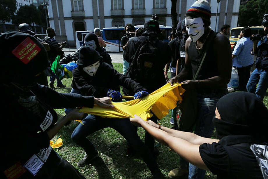 Masked anti-World Cup protesters rip apart a Brazilian national team soccer jersey during a demonstration, in downtown Rio de Janeiro, Brazil, Thursday, June 12, 2014, hours before the first World Cup match was to be played in Sao Paulo. (AP Photo/Leo Correa)