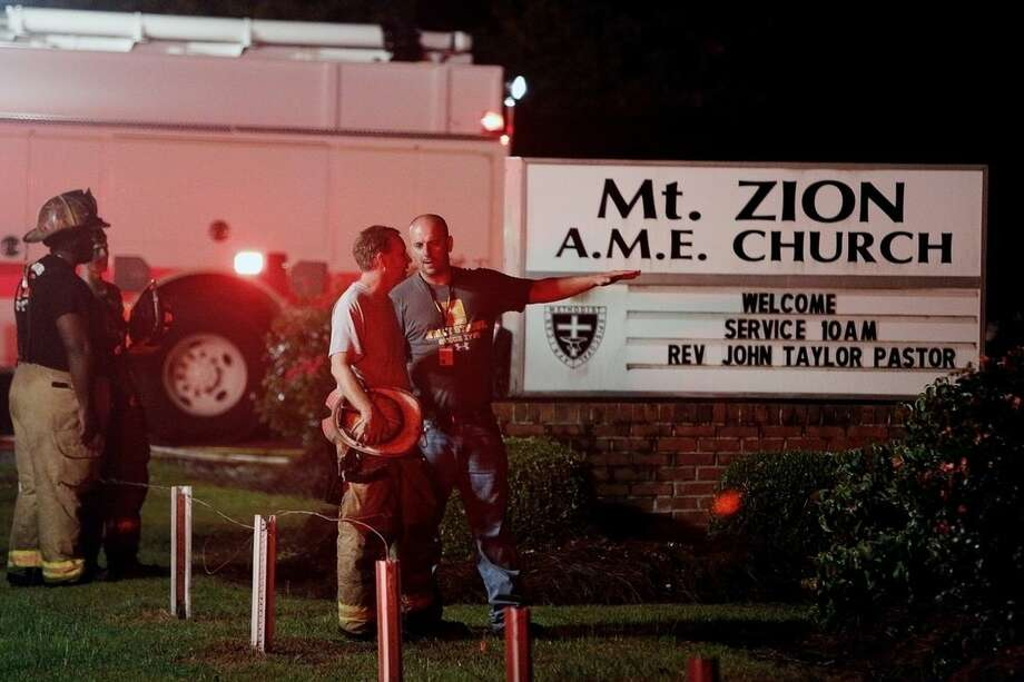 Public safety personnel talk outside Mount Zion African Methodist Episcopal church, late Tuesday, June 30, 2015, in Greeleyville, S.C. The African-American church, which was burned down by the Ku Klux Klan in 1995, caught fire late Tuesday night. (Veasey Conway/The Morning News via AP)