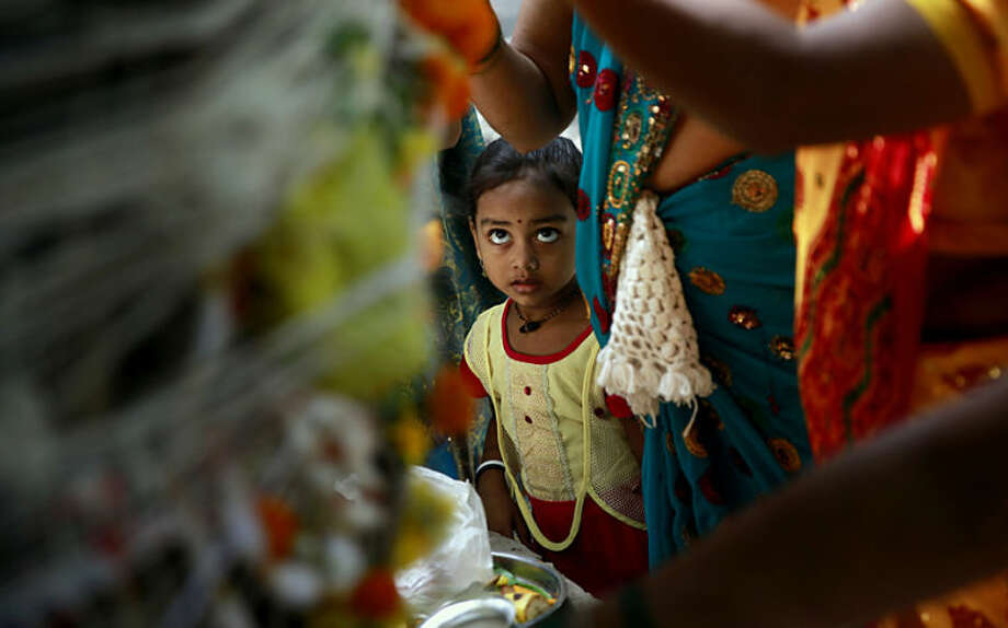 A Hindu girl watches her mother tie a cotton thread around a banyan tree during the festival of Vat Savitri in Mumbai, India, Thursday, June 12, 2014. Vat Savitri is celebrated by married Hindu women where they tie cotton threads around a banyan tree, pray for the longevity of their husbands and keep a day long fast. (AP Photo/Rafiq Maqbool)