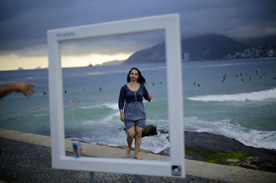 Tourists pose for photos in front of Brazil's famous Ipanema beach, Wednesday, June 11, 2014 in Rio de Janeiro, Brazil. The World Cup 2014 soccer tournament will be held in Brazil and starts on June 12.(AP Photo/Wong Maye-E)