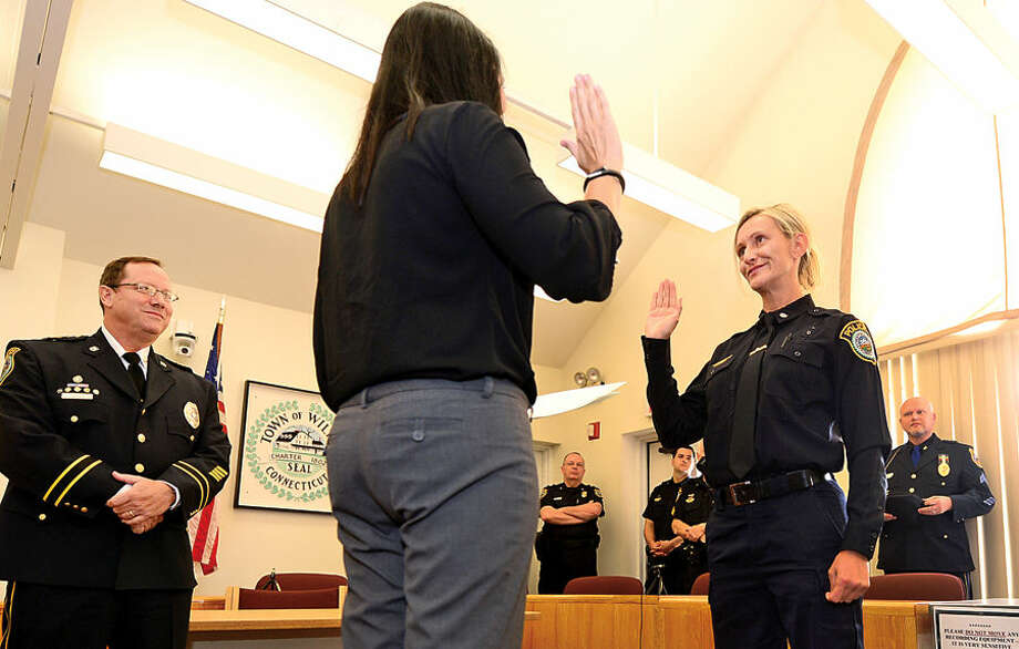 Hour photo / Erik Trautmann Wilton Police Officer Eva Zimnoch is promoted to the rank of Detective during a swearing-in ceremony conducted by Town Clerk, Laurie Kaback, Thursday morning.