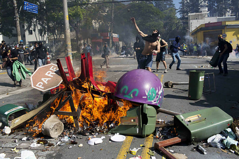 A masked man throws a stone towards riot policemen during a protest by people demanding better public services and against the money spent on the World Cup soccer tournament in Sao Paulo, Brazil, Thursday, June 12, 2014. Brazilian police clashed with anti-World Cup protesters trying to block part of the main highway leading to the stadium that hosts the opening match of the tournament. (AP Photo/Rodrigo Abd)