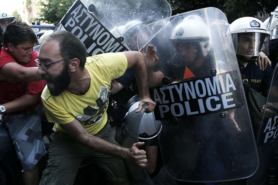 Protesters scuffle with riot police outside the Finance Ministry headquarters in central Athens, on Thursday, June 12, 2014. The scuffles came during a protest by former ministry cleaning staff, who lost their jobs last year. The protesters were angry at a court decision temporarily freezing a previous ruling in favor of their being re-hired. The bailed-out country's central bank said Thursday that Greece's economy is expected to grow about 0.5 percent this year after a punishing 6-year recession, but warned that there must be no slackening in the pace of reforms. (AP Photo/Petros Giannakouris)