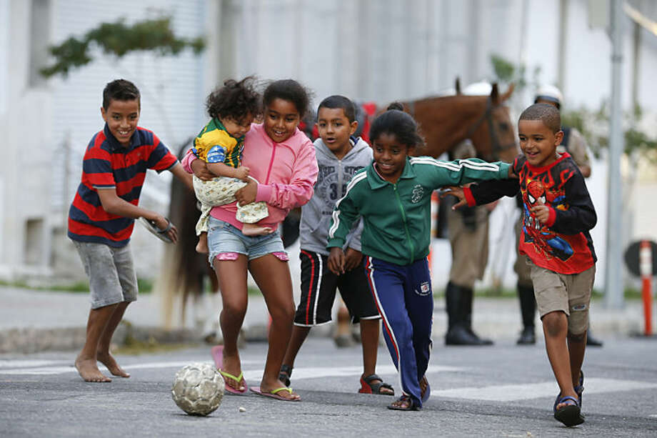 Children kick around a soccer ball outside the Independencia Stadium in Belo Horizonte, Brazil, Wednesday, June 11, 2014. The 2014 World Cup is set to begin Thursday, with Brazil and Croatia competing in the opening match in Sao Paulo. (AP Photo/Victor R. Caivano)