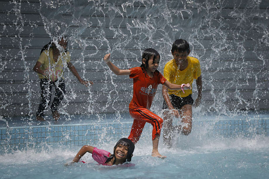 Children play in the pool in front of Malaysia's landmark Petronas Twin Towers in Kuala Lumpur, Malaysia, Thursday, June 12, 2014. (AP Photo/Vincent Thian)