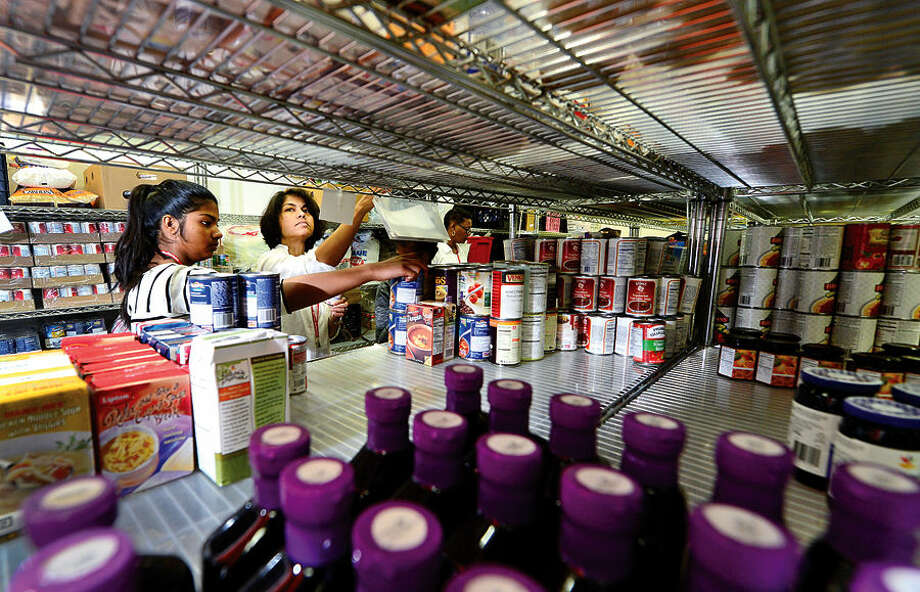 Hour photo / Erik Trautmann Person to Person volunteers Chhawa Dagli, right, and her daughter, Kavya, 13, stock shelves Thursday afternoon. Person to Person is seeking food donations as summer donations fall off and need tends to rise.