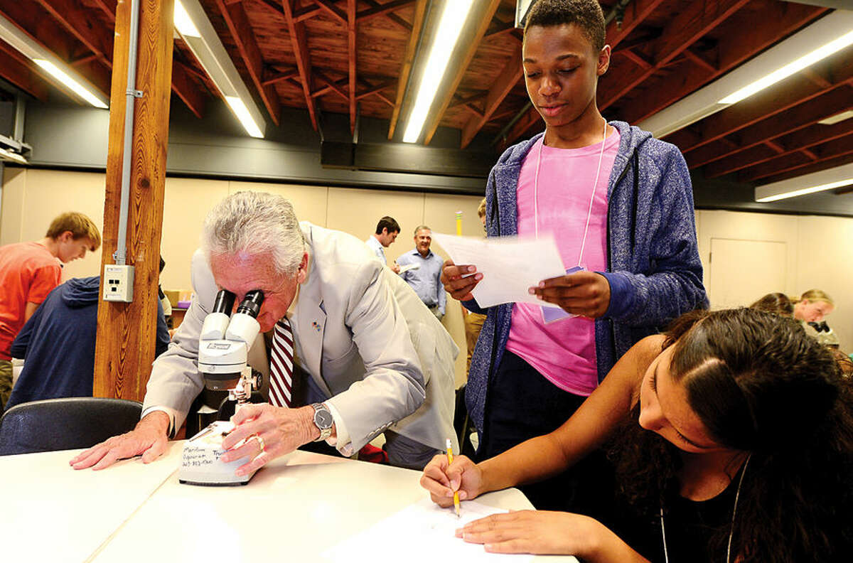 Hour photo / Erik Trautmann Norwalk Mayor Harry Rilling looks through a microscope as 8th and 9th graders including Luca Napoli-Bulteryst and Kiana Rodriguez participate in the