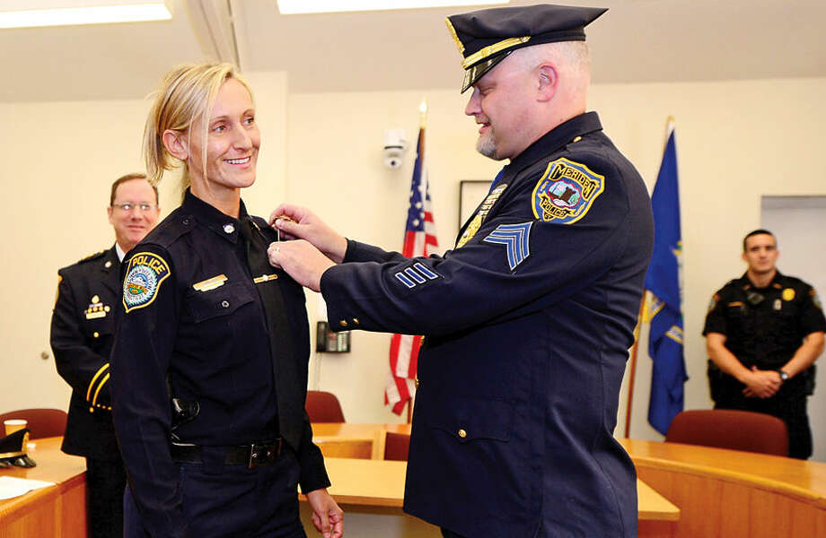 Hour photo / Erik Trautmann Wilton Police Officer Eva Zimnoch is pinned by her brother, Meriden police seargent Lester Zimnoch, after being promoted to the rank of Detective during a swearing-in ceremony Thursday morning.
