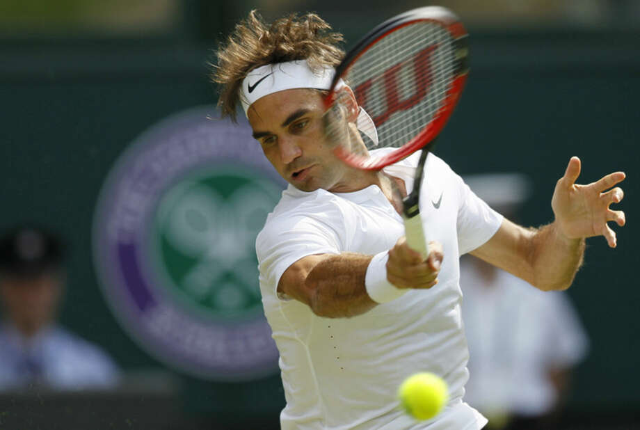 Roger Federer of Switzerland returns a ball to Sam Querrey of the United States during their singles match at the All England Lawn Tennis Championships in Wimbledon, London, Thursday July 2, 2015. (AP Photo/Pavel Golovkin)