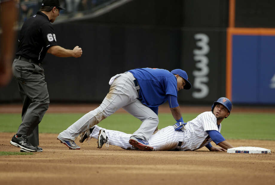 Chicago Cubs shortstop Starlin Castro, center, keeps his glove on New York Mets' Johnny Monell, right, as he reacts to being called out at second base during the fifth inning of the baseball game at Citi Field, Thursday, July 2, 2015 in New York. (AP Photo/Seth Wenig)