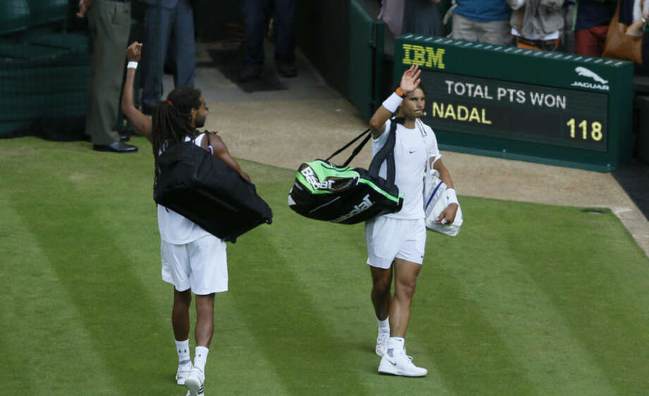 Rafael Nadal of Spain, right, and Dustin Brown of Germany leave the court after Brown defeated Nadal in their singles match at the All England Lawn Tennis Championships in Wimbledon, London, Thursday July 2, 2015. (AP Photo/Kirsty Wigglesworth)
