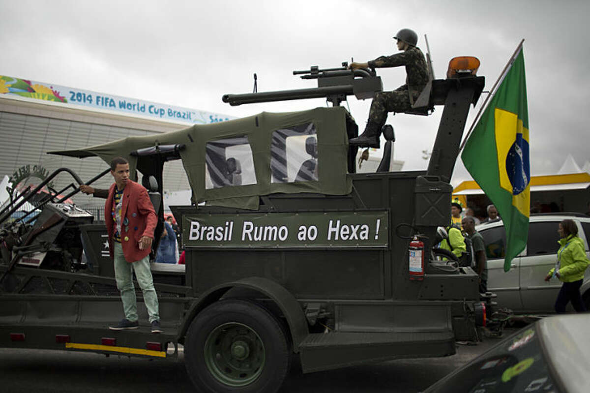 A Brazil soccer fan performs on a vehicle where a mannequin soldier rides at the top and the side reads in Portuguese