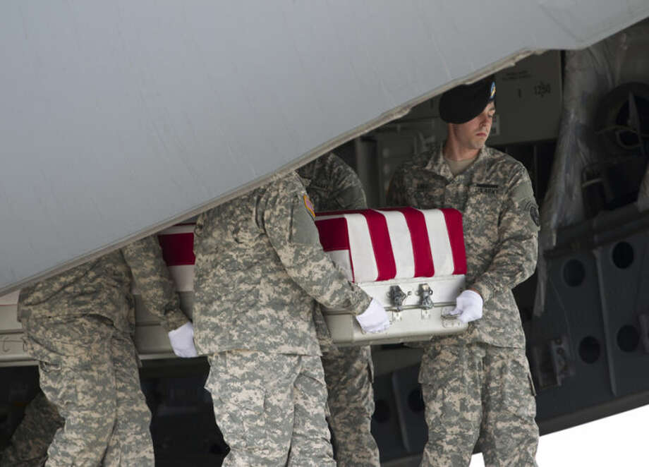 An Army carry team carries the transfer case containing the remains of Army Cpl. Justin R. Clouse, of Sprague, Wash., upon arrival at Dover Air Force Base, Del., on Thursday, June 12, 2014. The Department of Defense announced the death of Clouse who was supporting Operation Enduring Freedom in Afghanistan. ( AP Photo/Jose Luis Magana)