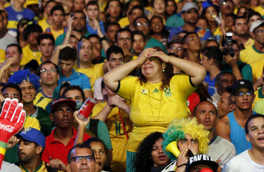A Brazilian fan grimaces as she watches the 2014 soccer World Cup opening game between Brazil and Croatia at the Fan Fest complex in Recife, Brazil, Thursday, June 12, 2014. After taking the early lead in the opening match of the international soccer tournament, Croatia fell 3-1 to the five-time champion Brazil. (AP Photo/Dolores Ochoa)