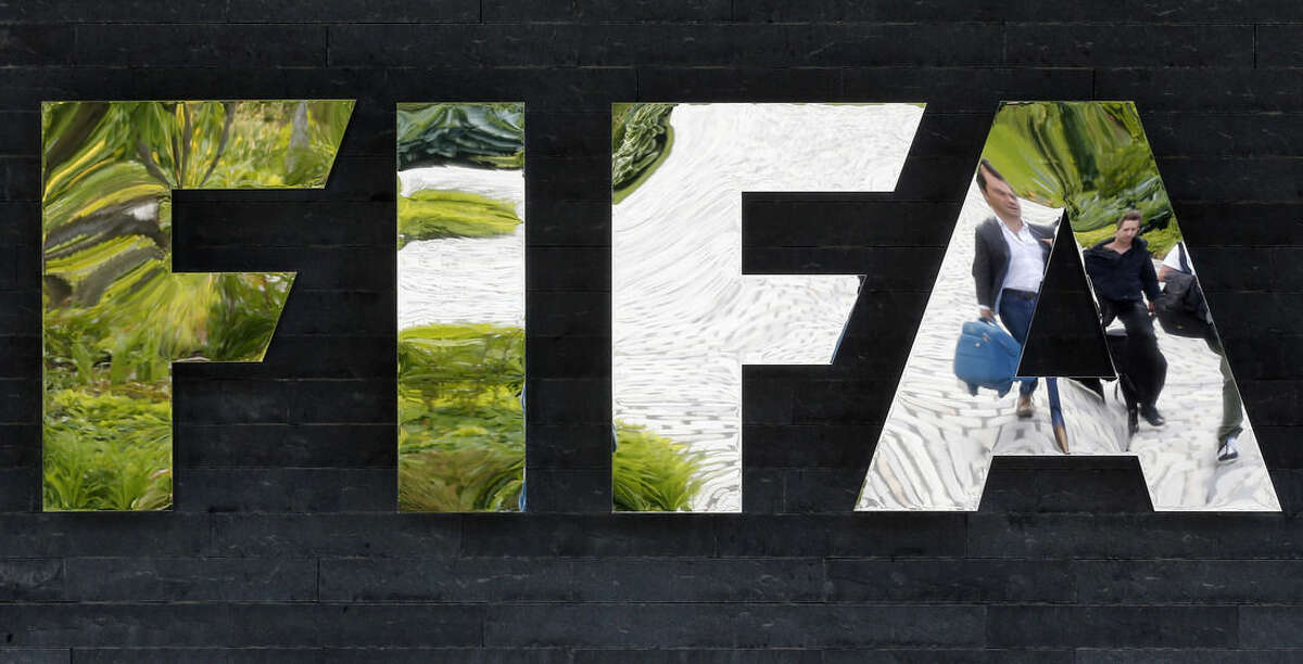 FILE - In this May 27, 2015, file photo, two persons are reflected in the FIFA logo at the FIFA headquarters in Zurich, Switzerland. The United States has submitted a formal request for Switzerland to extradite seven FIFA officials arrested as part of a corruption probe in Zurich in May, Swiss officials said Thursday, July 2, 2015. (AP Photo/Michael Probst, File0