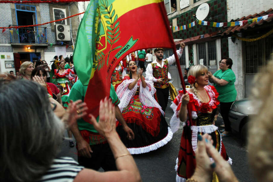 Dancers of the Mouraria neighborhood are greeted as they take part in Lisbon's popular contest during Saint Anthony festivities, in Lisbon, Thursday, June 12, 2014. During the contest, Lisbon's neighborhood groups compete for the best performance, costume design, music and choreography. People celebrate the festivities of the Day of Saint Anthony, who is the Lisbon's patron saint, by dancing and eating outside in colorfully decorated downtown streets. (AP Photo/Francisco Seco)
