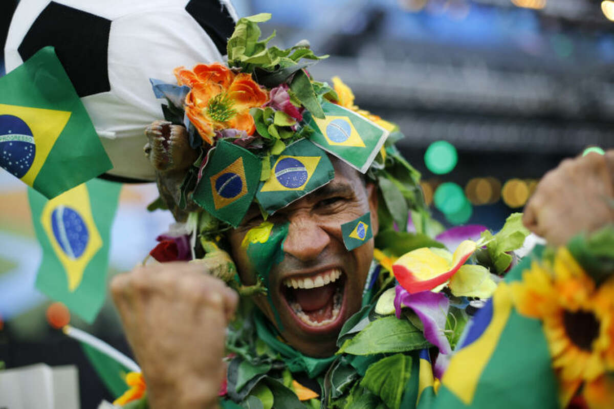 A Brazil soccer fan covered in flowers and his nation's flag cheers inside the FIFA Fan fest area before the start of the World Cup openes between Brazil and Croatia on Copacabana beach, Rio de Janeiro, Brazil, Thursday, June 12, 2014. After taking the early lead in the opening match of the international soccer tournament, Croatia fell 3-1 to the five-time champion Brazil. (AP Photo/Silvia Izquierdo)