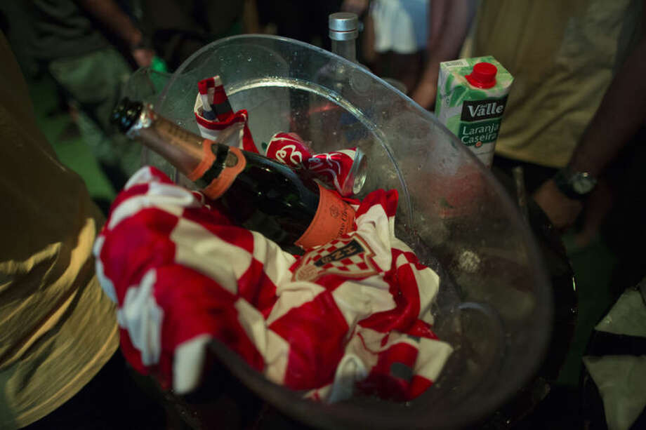 An empty wine bottle and a Croatian national flag sit in an ice bowl during a World Cup viewing party at the Jockey Club, in Rio de Janeiro, Brazil, Thursday, June 12, 2014. After taking the early lead in the opening match of the international soccer tournament, Croatia fell 3-1 to the five-time champion Brazil. (AP Photo/Leo Correa)