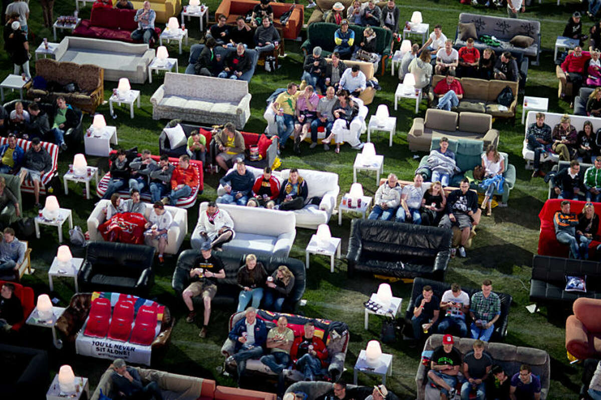 German soccer fans watch the opening game of the soccer World Cup 2014 while sitting on sofas in the 1.FC Union stadium in Berlin, Thursday, June 12, 2014. (AP Photo/Axel Schmidt)