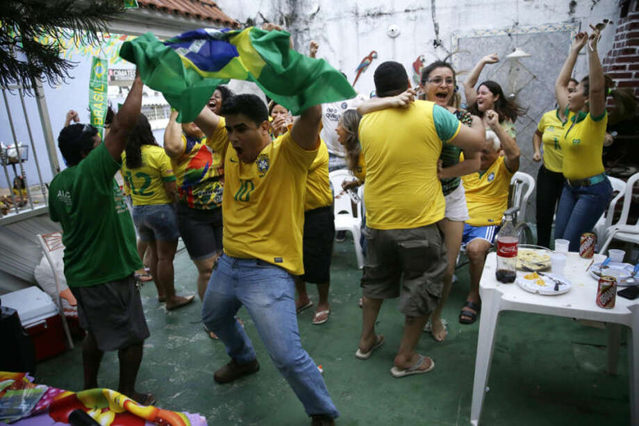 Soccer fans celebrate on the patio of a private residence as they watch a live broadcast of the goal scored by Brazilian midfielder Oscar in the World Cup opening match against Croatia, in Manaus, Brazil, Thursday, June 12, 2014. After taking the early lead in the opening match of the international soccer tournament, Croatia fell 3-1 to the five-time champion Brazil. (AP Photo/Martin Mejia)