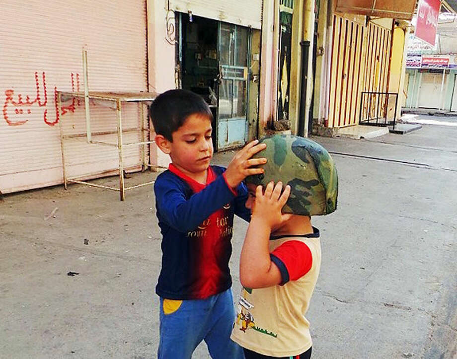 Children play with an Iraqi Army helmet left behind after militants from the al-Qaida-inspired Islamic State of Iraq and the Levant (ISIL) took over the northern city of Mosul, Iraq, Friday, June 13, 2014. Iraqi officials say al-Qaida-inspired militants who this week seized much of the country's Sunni heartland have pushed into an ethnically mixed province northeast of Baghdad, capturing two towns there. The writing on the metal shutters at left advertises a shop for sale. (AP Photo)