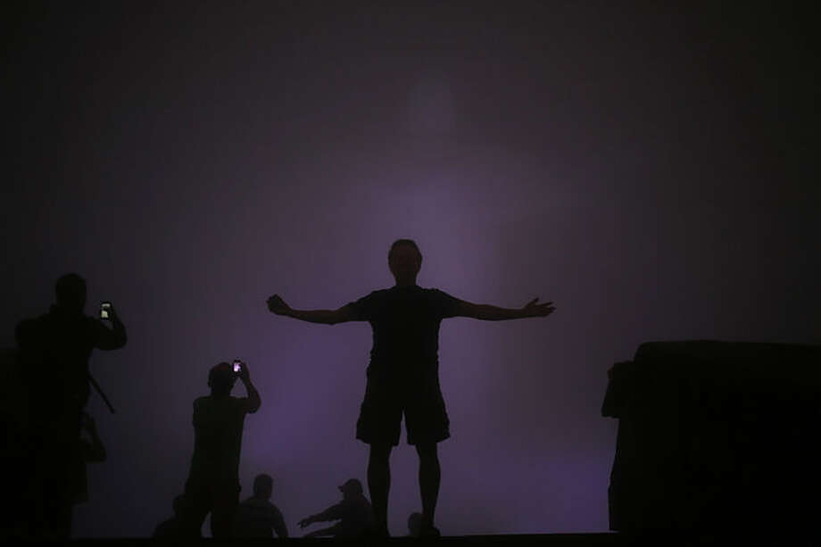 Tourists stand below the Christ the Redeemer statue while it is covered by heavy fog, in Rio de Janeiro, Brazil, Wednesday, June 11, 2014. The World Cup soccer tournament starts Thursday with Brazil facing Croatia in the opening game. (AP Photo/Hassan Ammar)