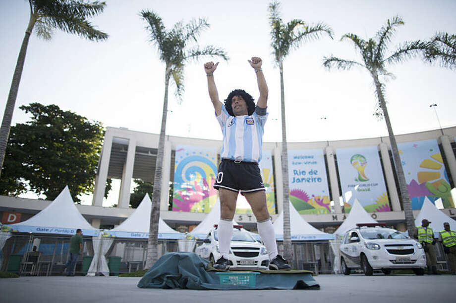 Street performing mime, Daniel Gonzalez, 35, who is dressed to resemble Argentine soccer great Diego Armando Maradona, gestures to the people who walk past him, in front of Maracana stadium, Rio de Janeiro, Brazil, Wednesday, June 11, 2014. The World Cup soccer tournament starts Thursday. (AP Photo/Leo Correa)