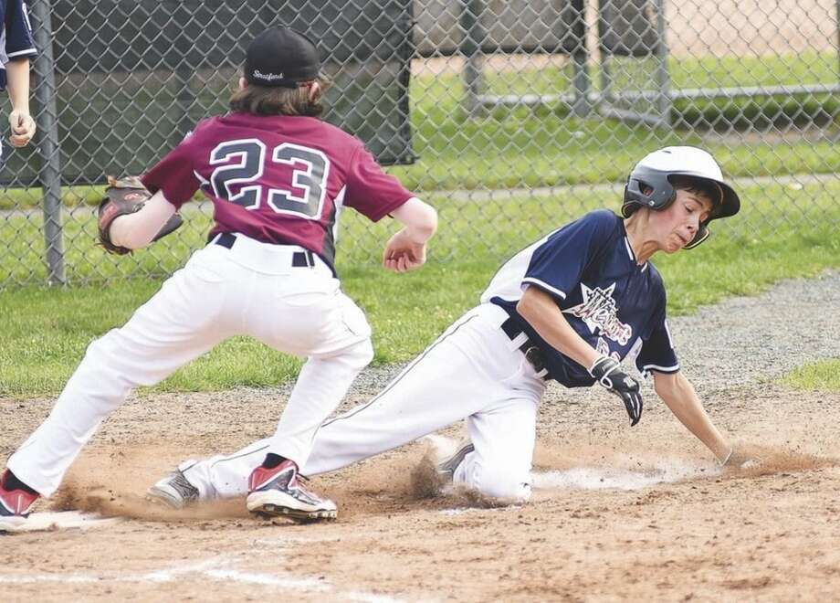 Hour photo/John NashWestport Little League 12-year-old All-Star Matt Gervasio, right, slides safely into home to score on a wild pitch as Stratford pitcher Mike Hoffman waits for the throw from the back stop during Thursday's District 2 tournament game at Unity Park in Trumbull.
