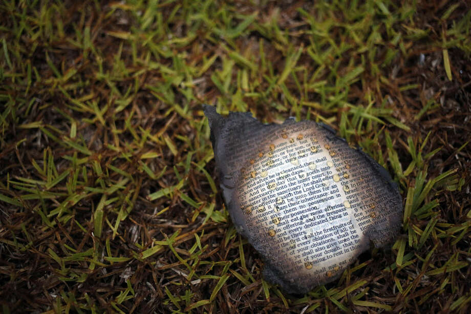 A charred bible page is seen outside Mount Zion African Methodist Episcopal church, Wednesday, July 1, 2015, in Greeleyville, S.C. The African-American church, which was burned down by the Ku Klux Klan in 1995, caught fire Tuesday night, but authorities said arson is not the cause. (Veasey Conway/The Morning News via AP)