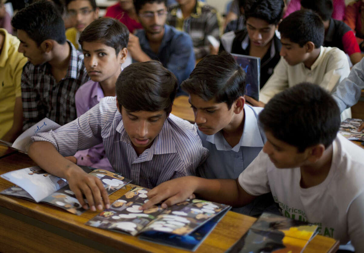 In this photo taken Monday, June 8, 2015, Pakistani students study over a comic book regarding counterterrorism distributed by a non-government organization run by Gauher Aftab at a local school in Lahore, Pakistan. Aftab now works with a group called CFXcomics, which aims to counter extremist propaganda. His English comic book has been translated into Urdu. (AP Photo/B.K. Bangash)